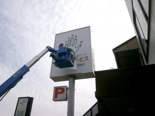 自立・野立て看板施工事例写真 愛知県 バケット内では1名が貼り作業、もう一人がバケットの操作を行います