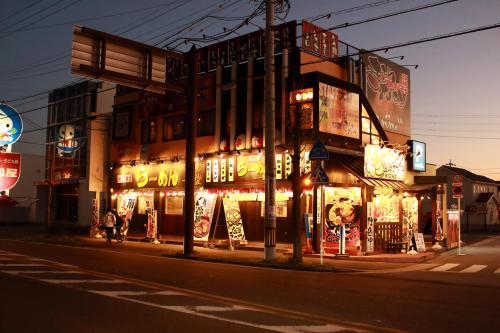 ファサード・壁面看板施工事例写真 愛知県 平看板、A型看板、既存看板表示面変更のシート貼り、日よけ幕、のぼり、LEDスポット12灯、駐車場看板など夜の様子