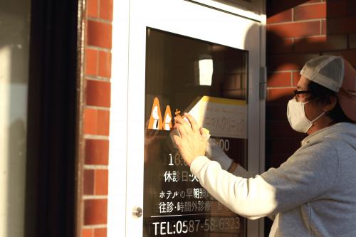 ウィンドウサイン・窓ガラス看板施工事例写真 愛知県 最後の仕上げ、転写シートを剥がす作業中