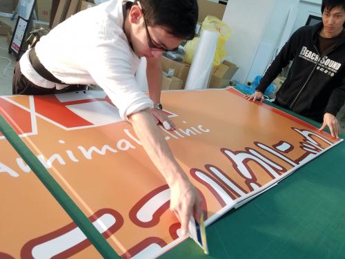 ファサード・壁面看板施工事例写真 愛知県 作業中 アルミ複合板にインクジェットプリントシート貼り込み風景