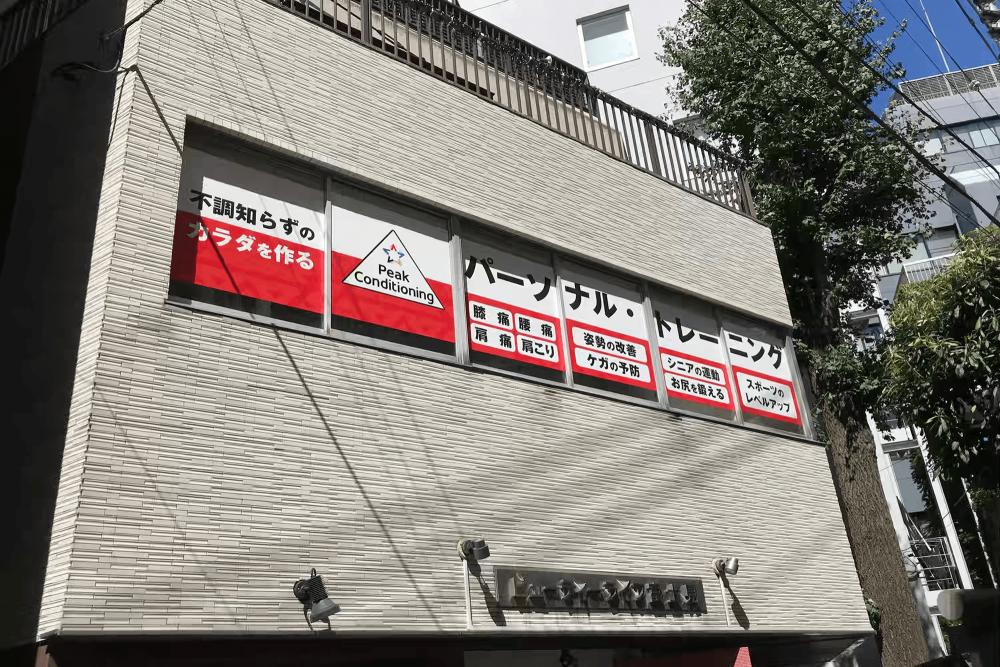 ウィンドウサイン・窓ガラス看板施工事例写真 東京都 当初は高所作業車でのお見積りをさせていただきましたが、公道ではなく私道だったため道路使用許可申請や警備員費用が不要になったことと、簡易足場(ローリングタワー)での作業が可能だったので費用を抑える事ができました