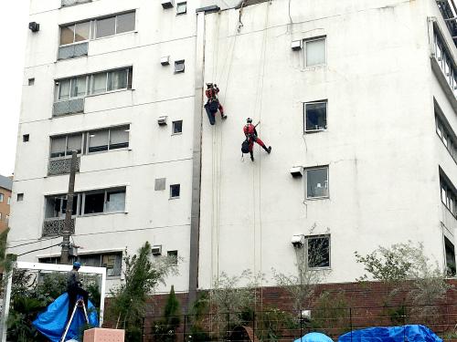 ファサード・壁面看板施工事例写真 神奈川県 屋上からロープで降り貼り付け位置を確認します