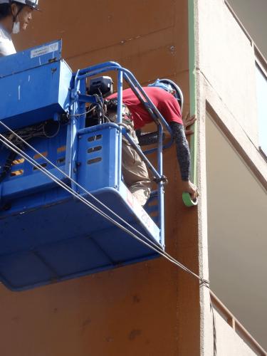 ファサード・壁面看板施工事例写真 愛知県 長期タイプの壁面シートのため壁面に専用のプライマーを塗布するため、位置だしも踏まえ養生テープを貼ります